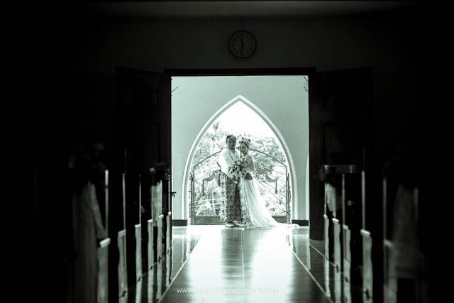 foto pengantin sedang berpose di depan gereja