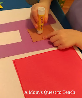 Putting together construction paper house craft