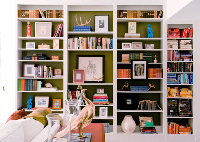 m design's living room with white built in book shelves with the back wall of the shef painted green