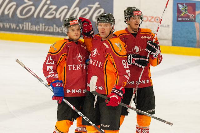 Trīs hokejisti apsveic viens otru pēc vārtu guvuma