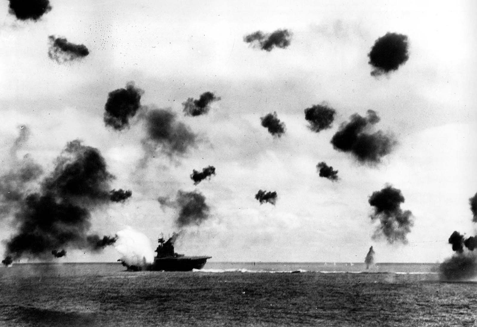 Smoke rises from the USS Yorktown after a Japanese bomber hit the aircraft carrier in the Battle of Midway on June 4, 1942. Bursts from anti-aircraft fire fill the air.