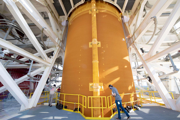 Engineers inspect the SLS core stage booster as it sits atop the B-2 Test Stand at NASA's Stennis Space Center in Bay St. Louis, Mississippi.
