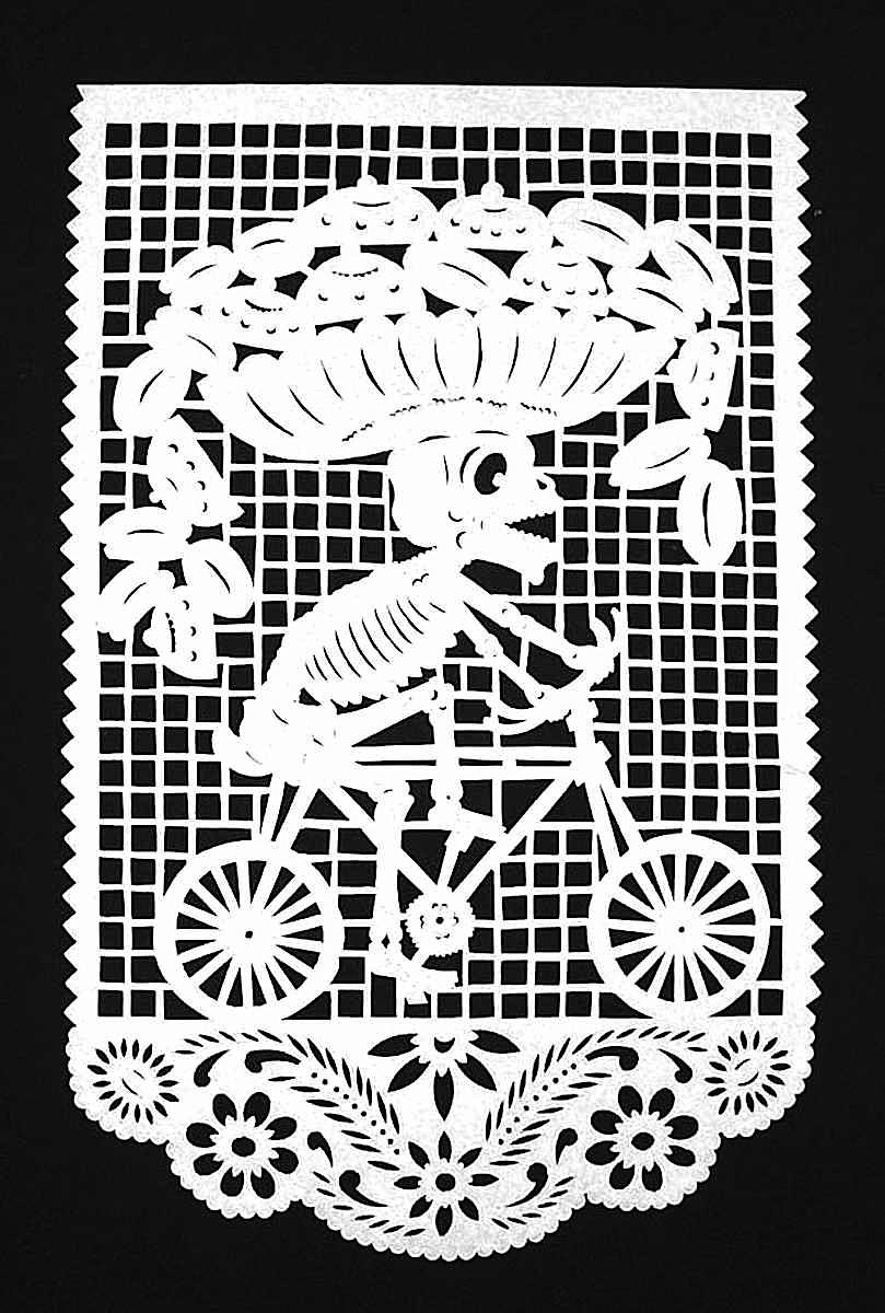 A papercut skeleton on a bicycle