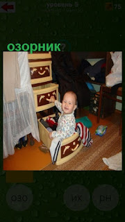 озорной ребенок открывает все ящики подряд в шкафу