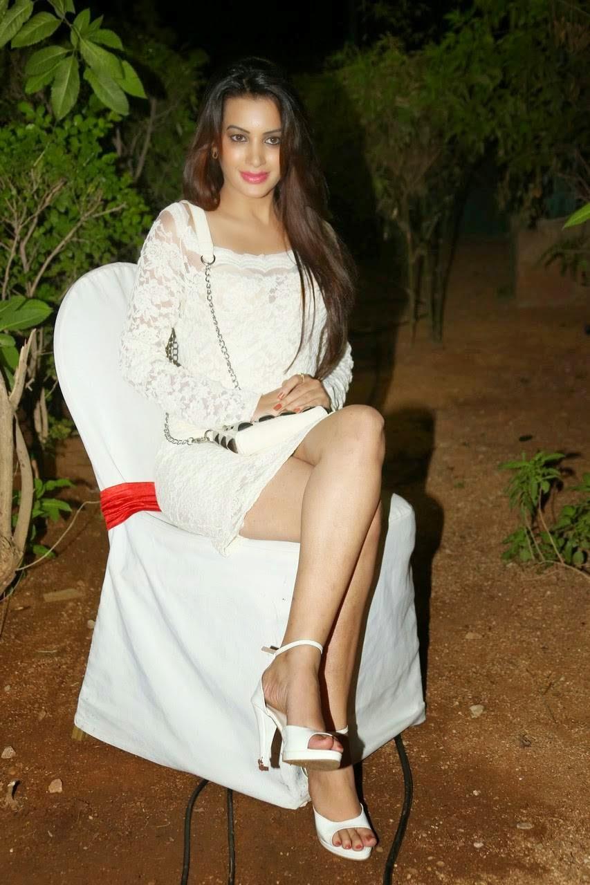 Diksha Panth Audio Launch Stills, Actress Diksha Panth Crossleg Sitting Pics in White Dress from Event