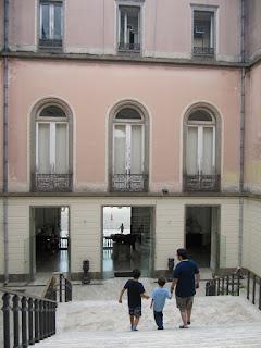 Foto de uma escadaria interna do prédio. Vê-se uma pedaço da escada de mármore e a parede levemente rosada.