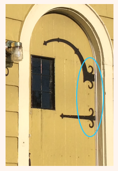 sears curlycue on iron strapping of door