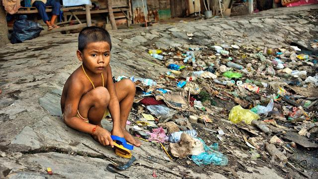 Enfant jouant prés d'un étang - dépotoir créé par les eaux usées et l'accumulation des ordures ménagères