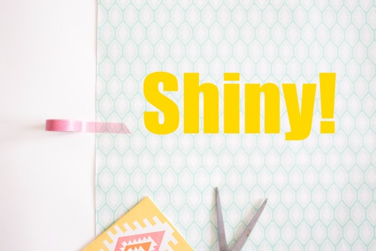 Banner reading Shiny! in deep yellow letters against a background of elongated pale blue-green honeycombs. A roll of translucent pink tape secures the background to a white border, while a pair of open scissors and a card printed with geometric designs in pale yellow, pale pink, and white peek into the shot along the bottom of the screen.