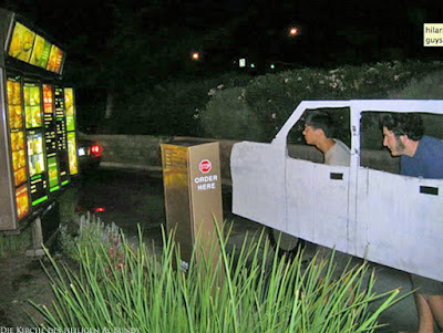 Lustige junge Männer mit selbstgebautem Auto in Drive Inn Restaurant