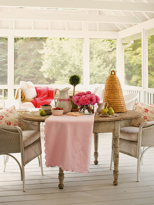 This white washed porch furniture is set for an afternoon tea party