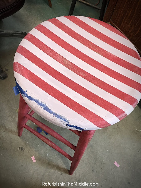 red tall stool with red and white stripes on seat