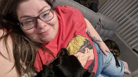 image of me lying on my couch, with Zelda the Black and Tan Mutt's head resting on my chest and Sophie the Torbie Cat curled up behind my outstretched legs