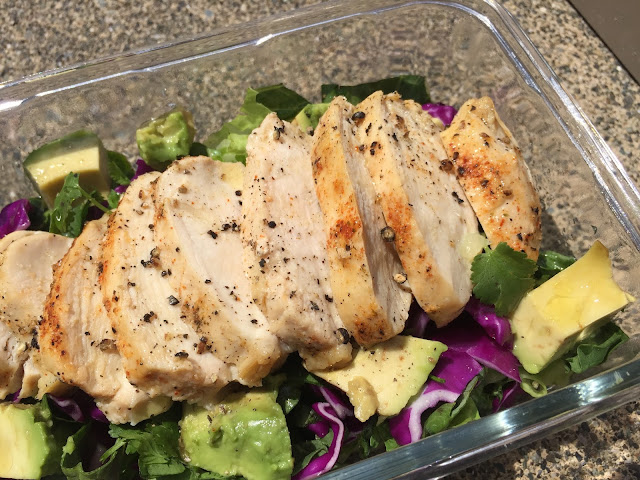 Close up shot of the Avocado Lemon Pepper Chicken Salad in a glass bowl on concrete