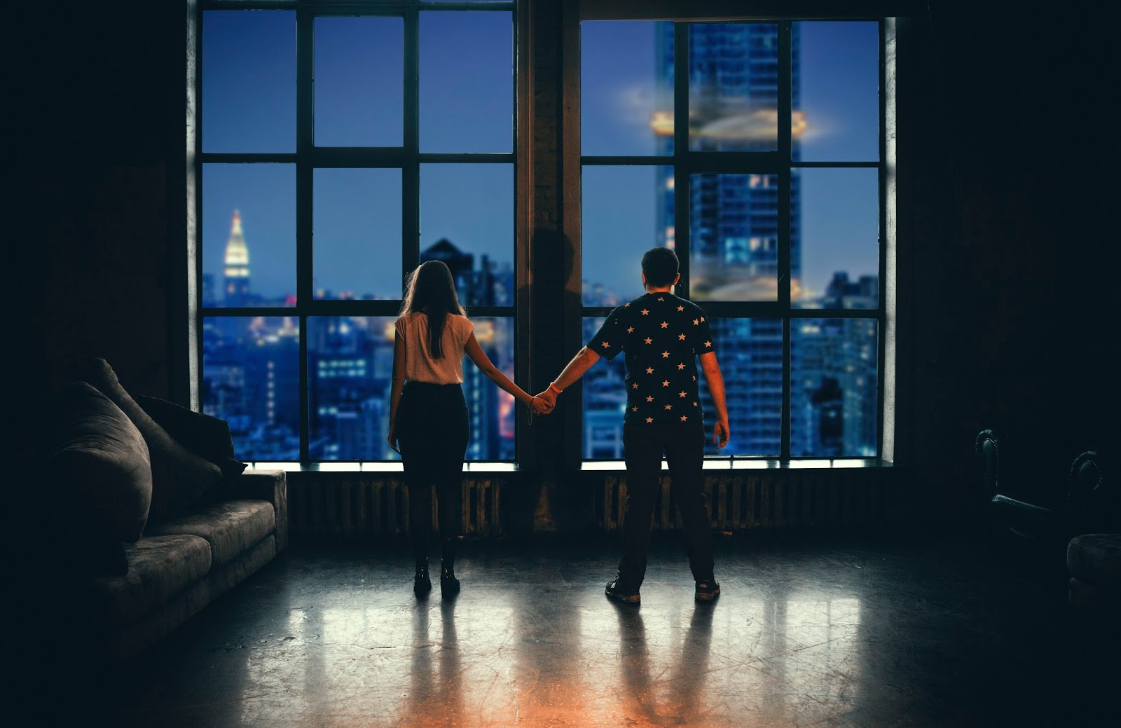 couple holding hands looking out of a skyscraper window over a brightly lit city