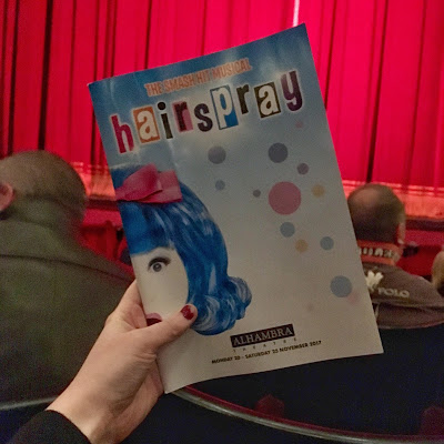 a hand holding up a blue Hairspray programme in front of red theatre curtains