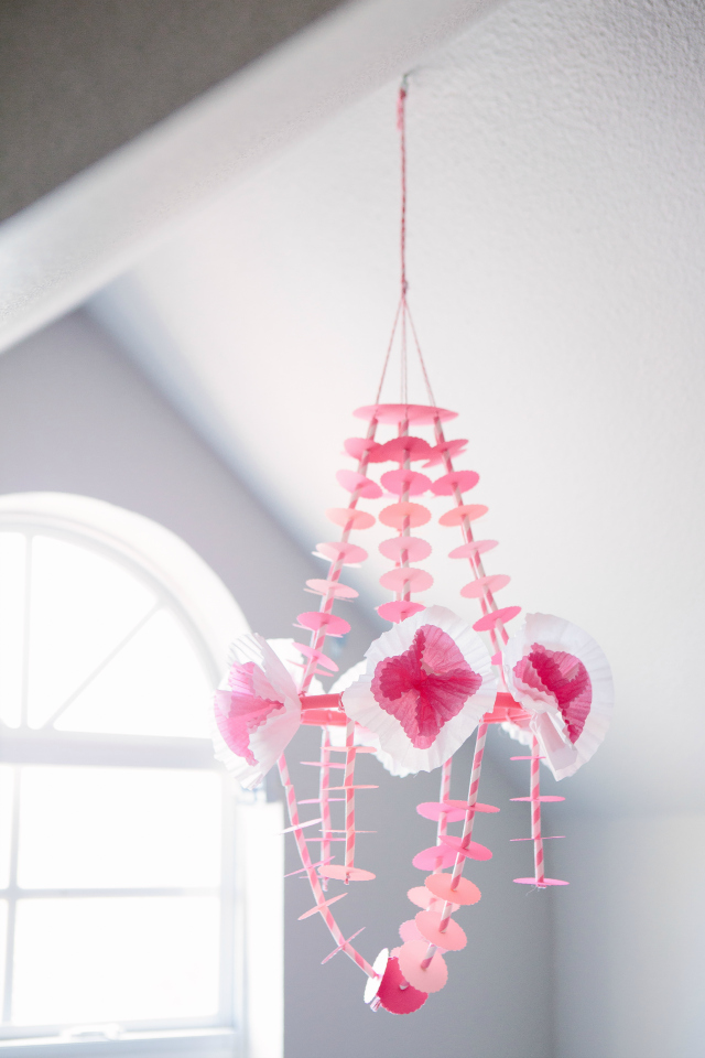 This delicate paper chandelier comes together easily with a paper punch, striped straws, and cupcake wrapper flowers! || http://designimprovised.com