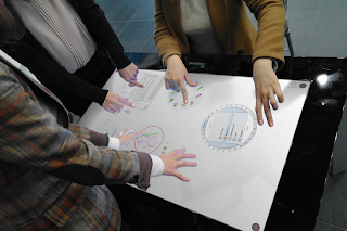 Three people standing around a digital table interacting with content on the table.