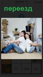 происходит переезд молодые люди в комнате с коробками и вещами