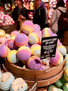 A selection of pink and purple spherical bath bombs with ridges all over them on a wide light brown rectangular shelf with a black board saying Groovy Kind of Love in white casual font on a bright background