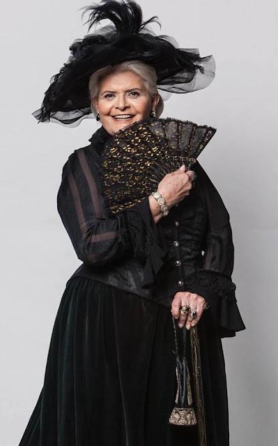 Madame Uraca, baronesa (Jussara Freire) Figurino escrava mãe vestido preto com leque