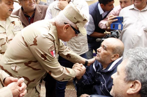 رئيس الأركان محمد فريد حجازي يتحدث إلى رجل في كرسي متحرك بالقرب من مركز اقتراع بالإسماعيلية في 28 مارس 2018