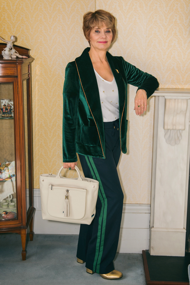 Image showing an over 40s woman in green velvet jacket and navy trousers with a green side stripe