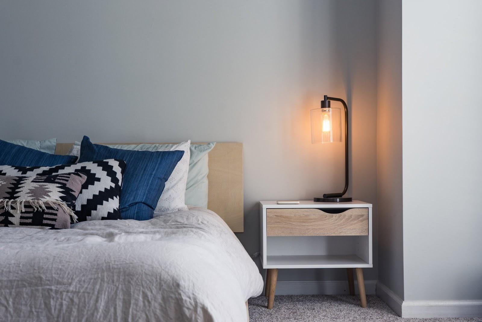 Szafka i oświetlenie to elementy obowiązkowe przy sypialnianym łóżku