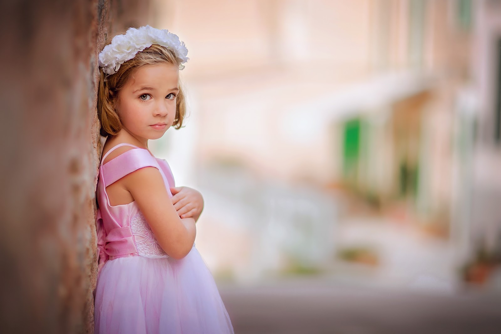 Canon Portrait of a young girl in a pink dress standing against a wall at Mallorca in Spain by Willie Kers