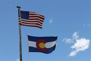 Sunny blue sky with the American flag and Colorado flag blowing in the wind on a flag pole.