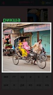 по улице едет рикша и везет пассажиров двух  женщин