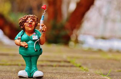 Imagen de una caricatura de una enfermera, en uniforme verde y jeringa con un corazón