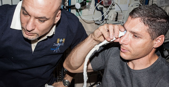 NASA astronaut Michael Hopkins (at right), Expedition 37 flight engineer, performs ultrasound eye imaging in the Columbus laboratory of the International Space Station. European Space Agency astronaut Luca Parmitano, flight engineer, assists. Credit: NASA