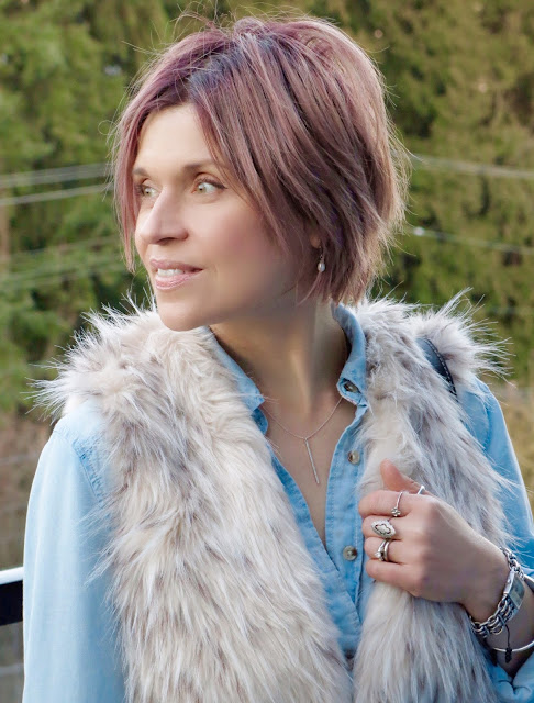 chambray shirt, faux-fur vest, and pink hair