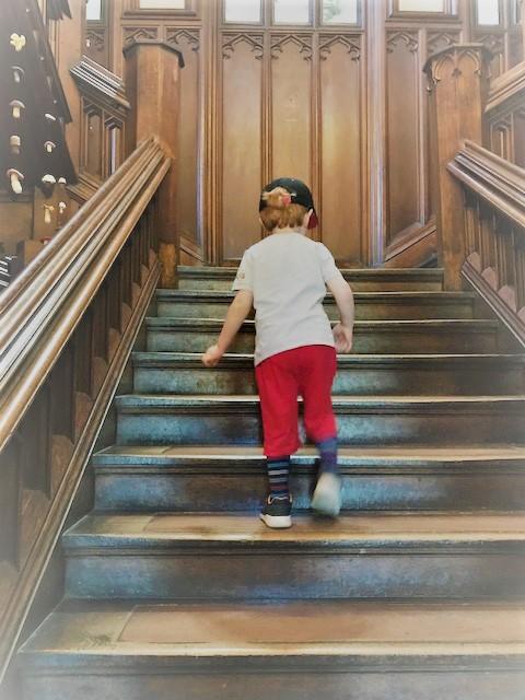 Little boy go up an oak staircase