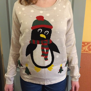 A light grey jumper, with a giant penguin wearing a red and green woolly hat and scarf, in a snow scene, with tiny Christmas trees.