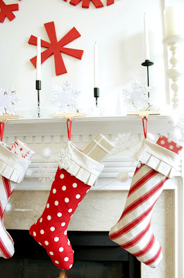 Red and white stocking on mantel with wooden red snowflakes wall art