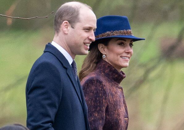 Kate Middleton wore a funnel neck coat, Stuart Weitzman knee-high boots,  feather fedora by Hicks and Brown, and carries Jaeger bag