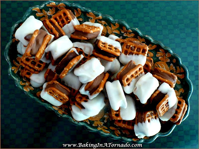 Pretzel Sandwich Snacks: Different flavored chocolates lightly melted between pretzels then partially dipped in vanilla candy melts. A perfect snack for any occasion. | Recipe developed by www.BakingInATornado.com | #recipe #chocolate #snack