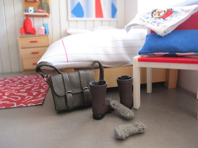 Modern one-twelfth scale miniature leather satchel, boots and socks dumped on the floor at the end of a bed.