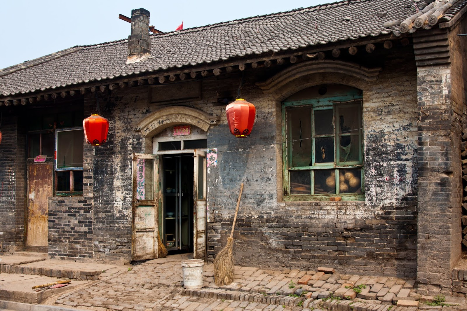 Superstições chinesas - vassoura de piaçava apoiada na parede de uma casa com lanternas vermelhas chinesas