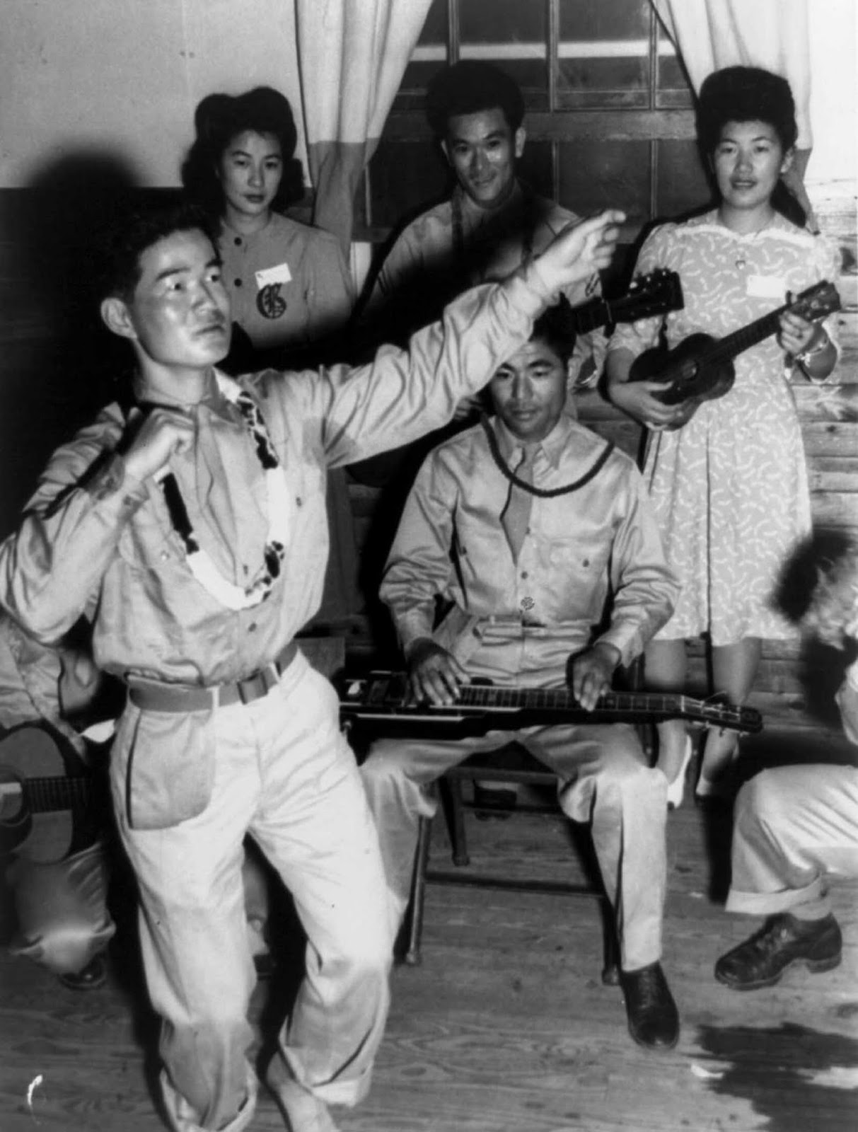 Private Harry Hamada does a hula dance with musical accompaniment. June, 1943.