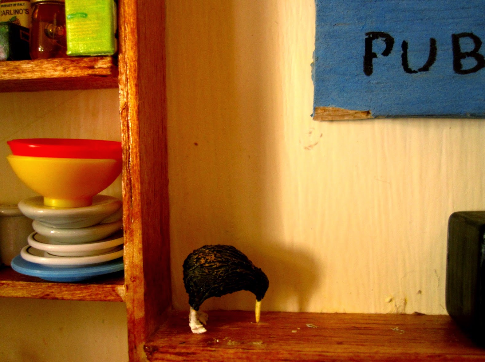 Dolls house miniature wall shelving with a kiwi ornament placed on it, next to a pile of plates and dishes  and a shelf of food items.