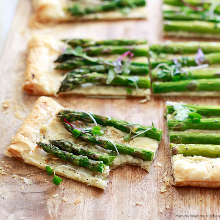 An easy asparagus tart recipe with puff pastry, lemon zest, and goat cheese style filling.
