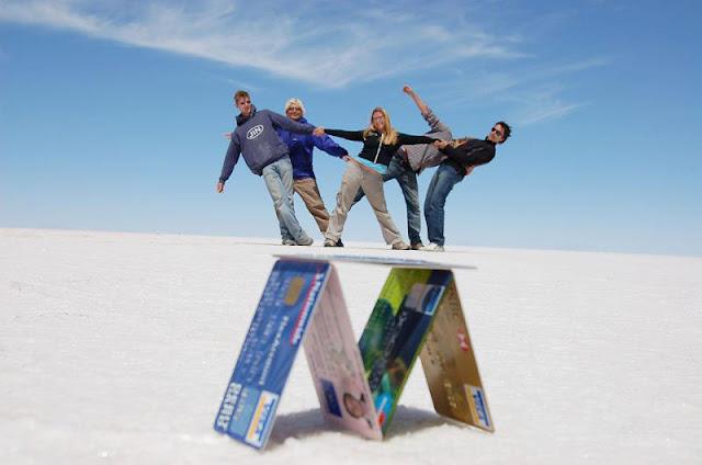 Üst üste dizilmiş kredi kartları üzerinde poz veren gençler