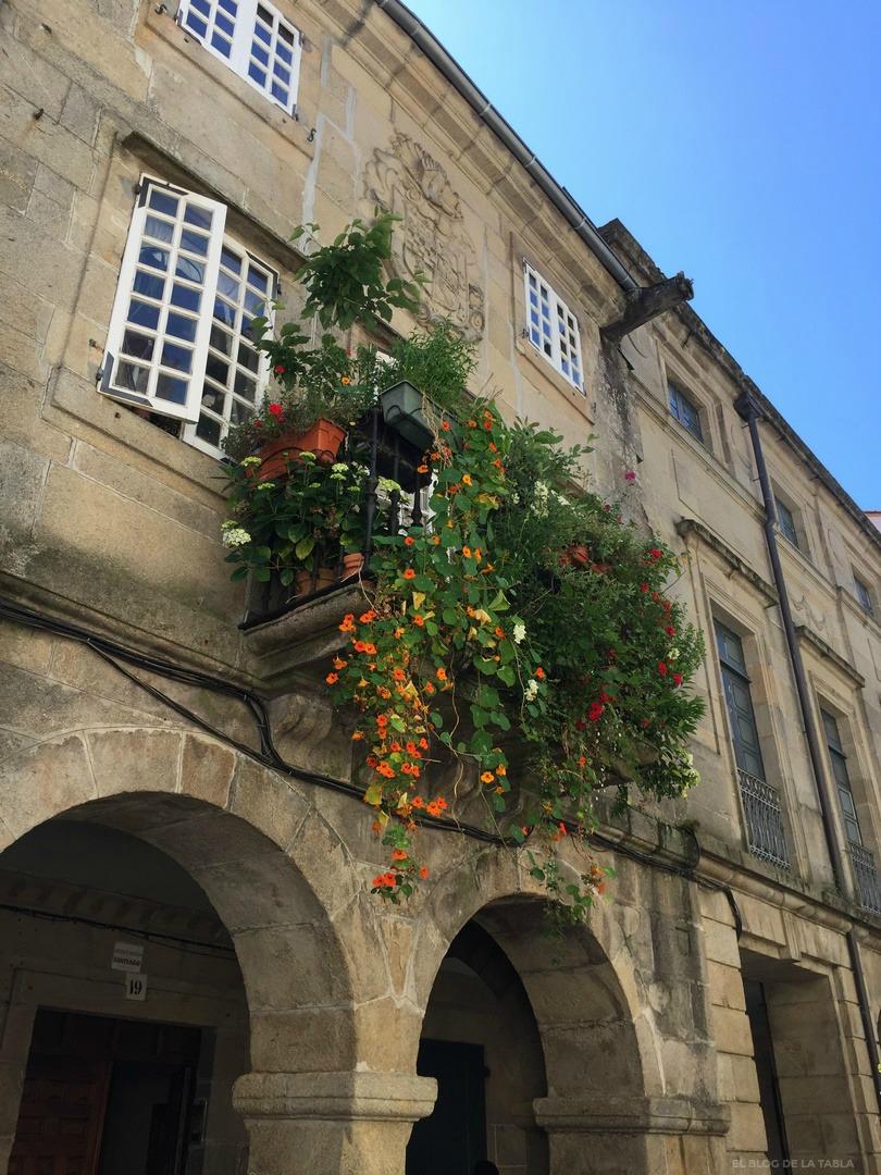 Fachada de piedra, soportales y balcon con plantas y flores