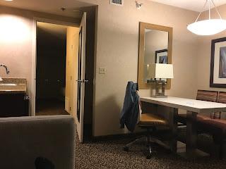 Stue med et skrivebord, noen stoler og en åpen dør.