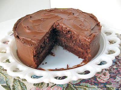 A Nigella\'s old fashioned chocolate cake resting on a white cake stand with a slice removed.