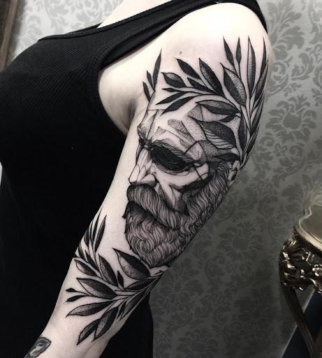 Artística manga da tatuagem. A tatuagem mostra um homem, que é, presumivelmente, um estudioso com uma coroa de folhas na cabeça. Ele parece estar fechando os olhos, como ele se ajoelhar na frente dele. (Foto: Fontes de imagem)