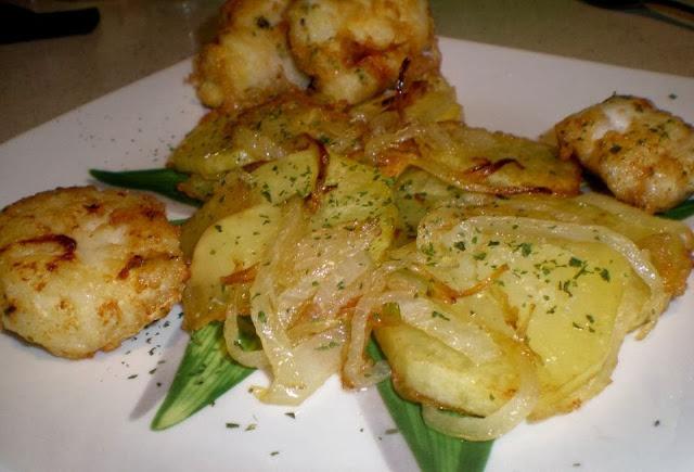 merluza frita al ajo y perejil con guarnición de patatas panaderas y cebolla